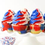 close up of red, white and blue cupcakes on a cake stand