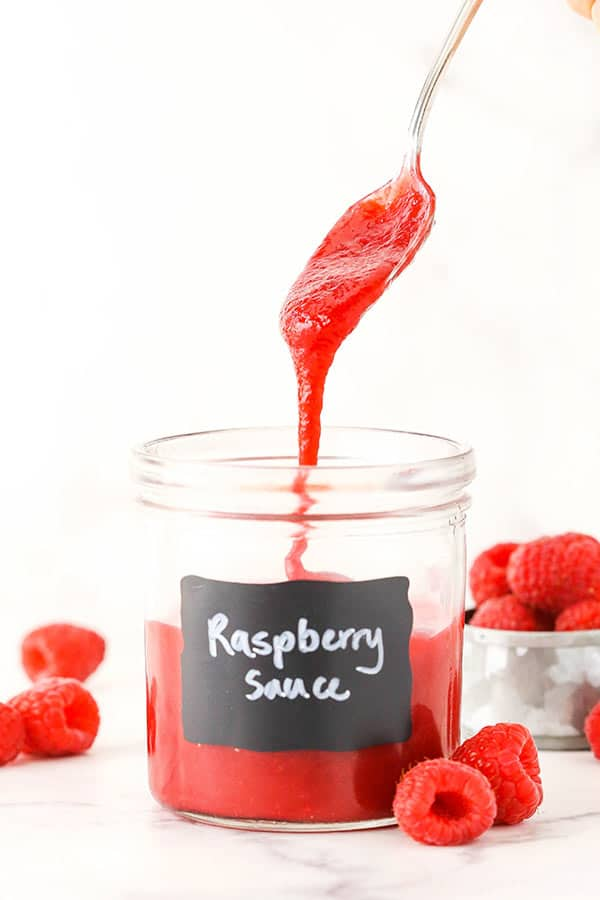 "raspberry sauce dripping off a spoon into a jar labeled ""raspberry sauce"""