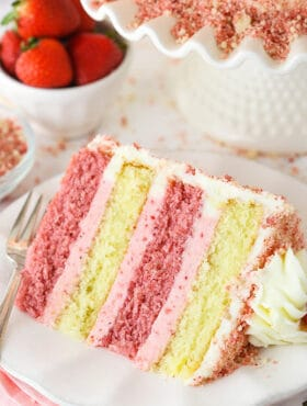 slice of strawberry crunchy cake with alternating layers of strawberry and vanilla cake