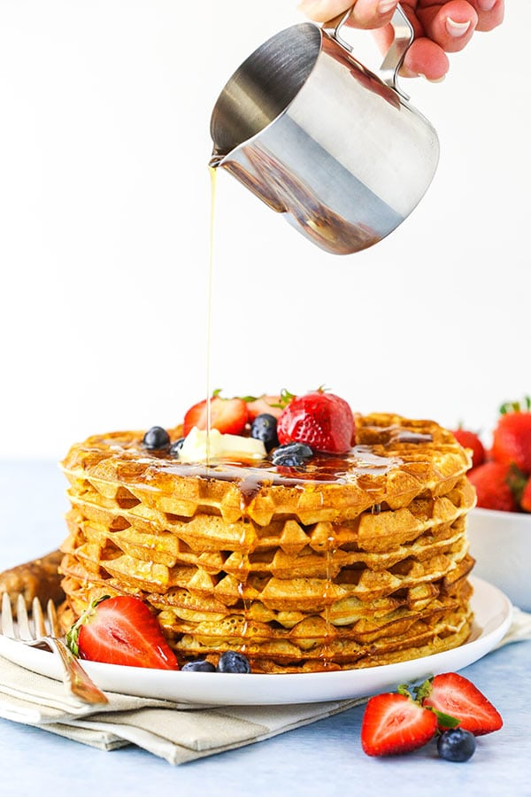 pouring syrup onto stack of waffles