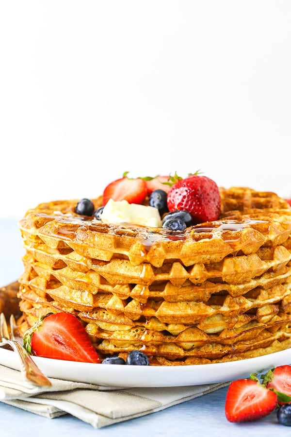 side close up of a stack of waffles with syrup