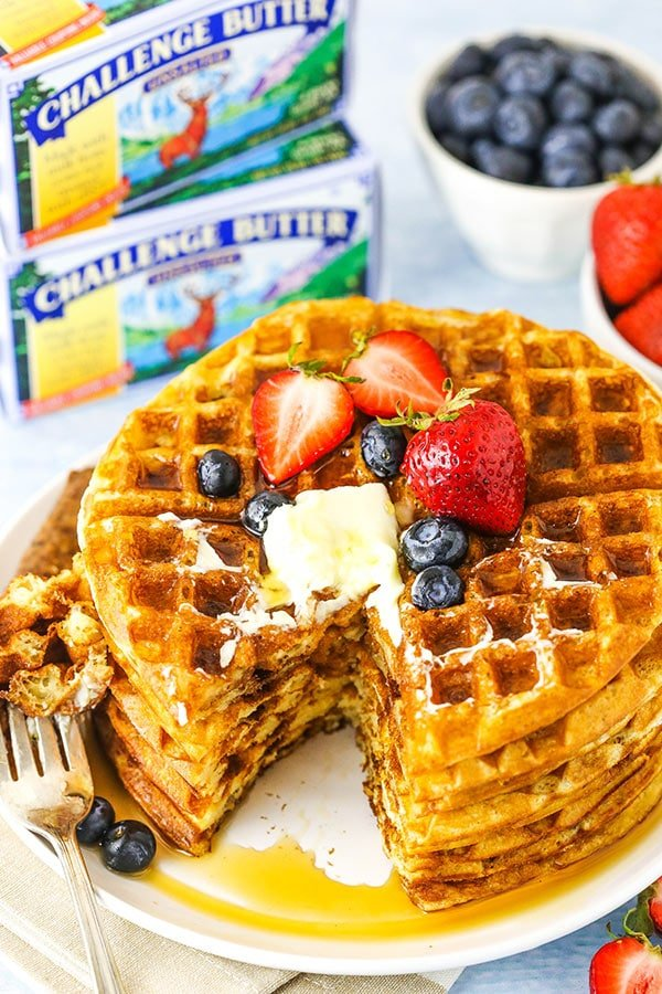 stack of waffles with a bite and challenge butter in background
