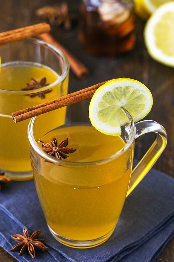 Two Cups of Hot Toddy Garnished with a Lemon Slice, a Cinnamon Stick and an Anise Star