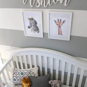 Ashton's Crib with A Zebra and Giraffe Painting On the Wall Above it