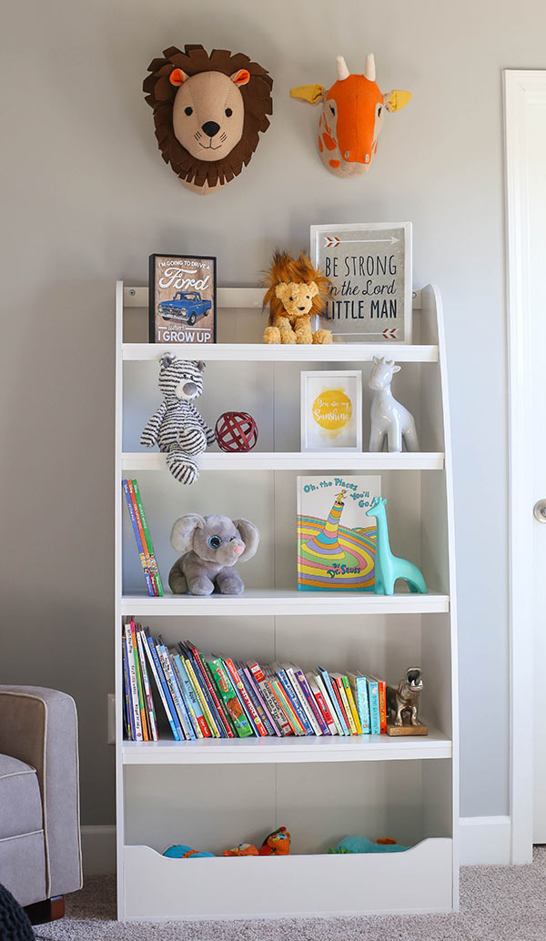 A White Shelf Filled with Baby Books and Animal-Themed Decorations