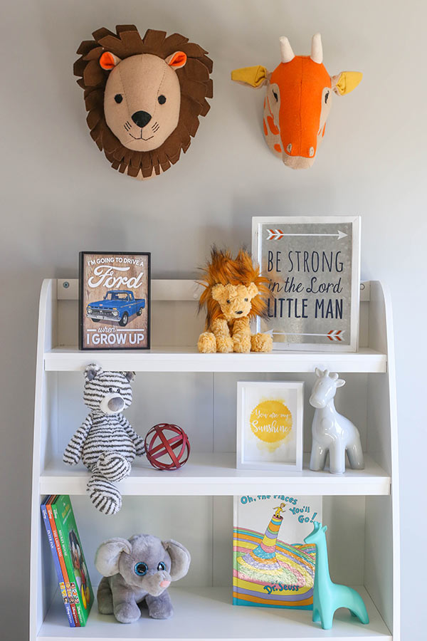 The Top Half of the Bookshelf With a Lion and Giraffe Head Above