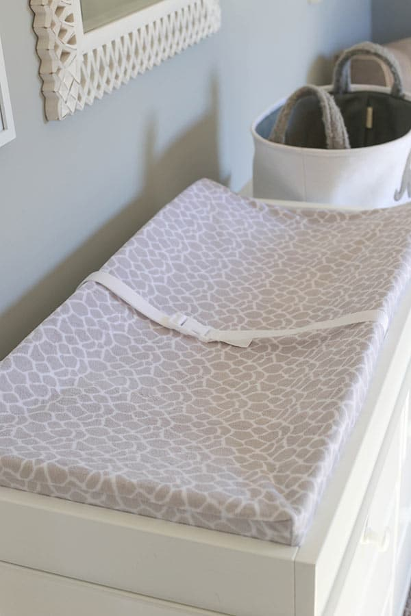 A White Changing Table with a Giraffe Patterned Changing Pad on Top