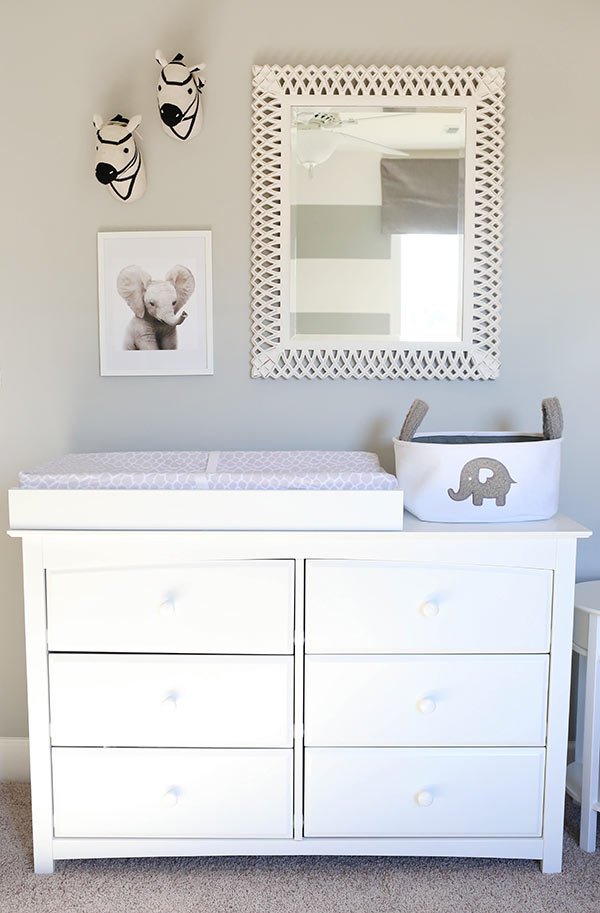 A White Dresser with a Changing Table on Top and a Mirror on the Wall Above