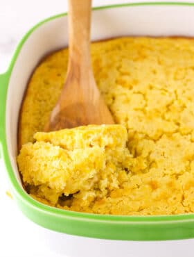 A Wooden Spoon Scooping out a Serving of Creamy Cornbread Casserole