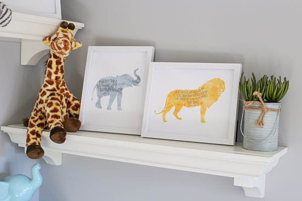 A Shelf with a Giraffe Toy, a Plant and Lion & Elephant Scripture Prints