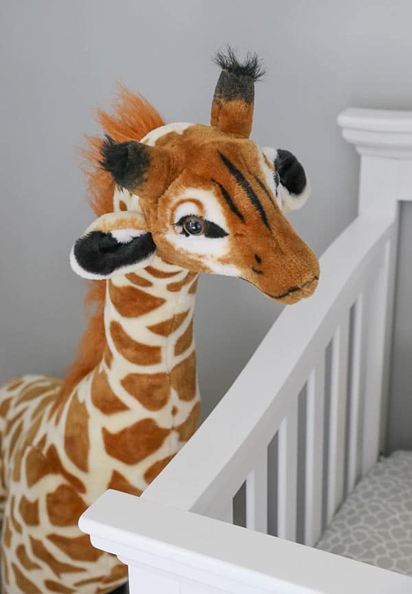 A Large Stuffed Giraffe Peeking Over Ashton's Crib