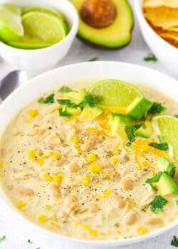 A Bowl of Instant Pot White Chicken Chili with Limes and Avocado
