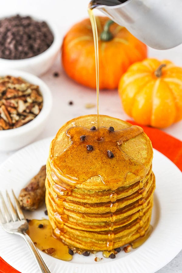 Pouring Maple Syrup Over a Pile of Pumpkin Pancakes