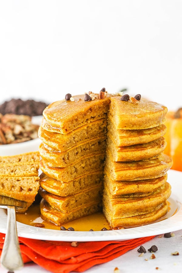 Stack of pumpkin pancakes on a white plate with syrup.