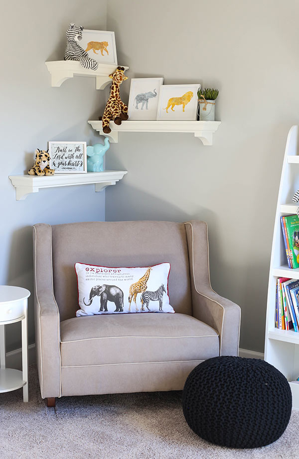 A Taupe Rocker with Three White Floating Shelves on the Wall Above it