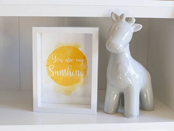 "A Ceramic Giraffe Beside a Print that Reads ""You are my Sunshine"""