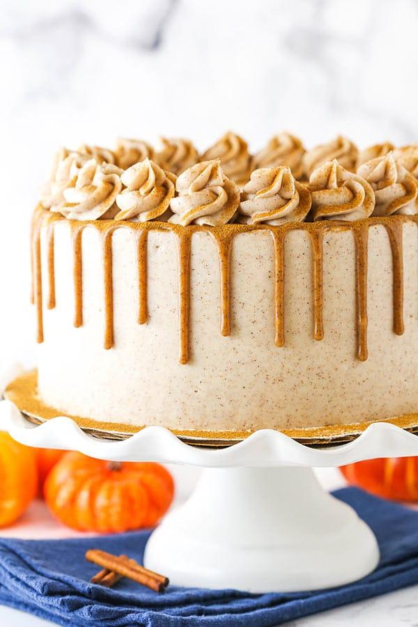 cinnamon sugar pumpkin cake with cinnamon drizzle on white cake stand