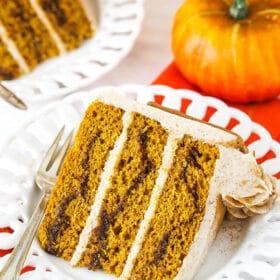slice of cinnamon sugar pumpkin layer cake with pumpkin in background