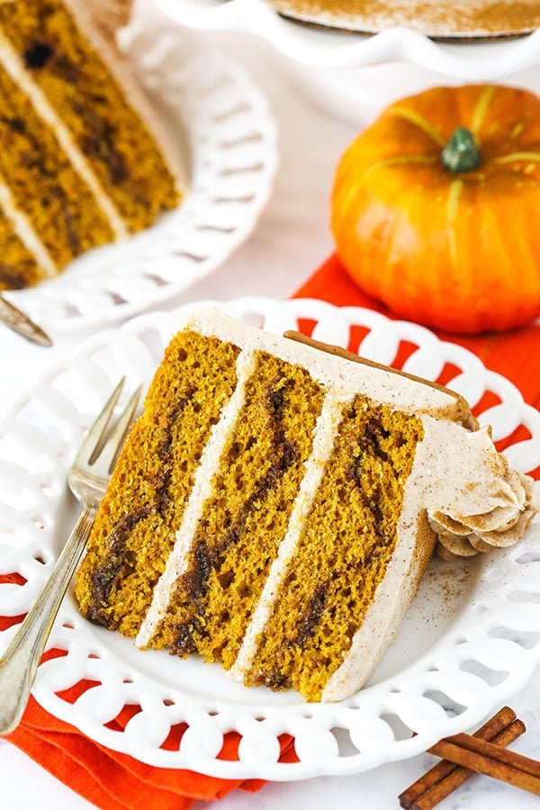slice of cinnamon sugar pumpkin layer cake with pumpkin in background