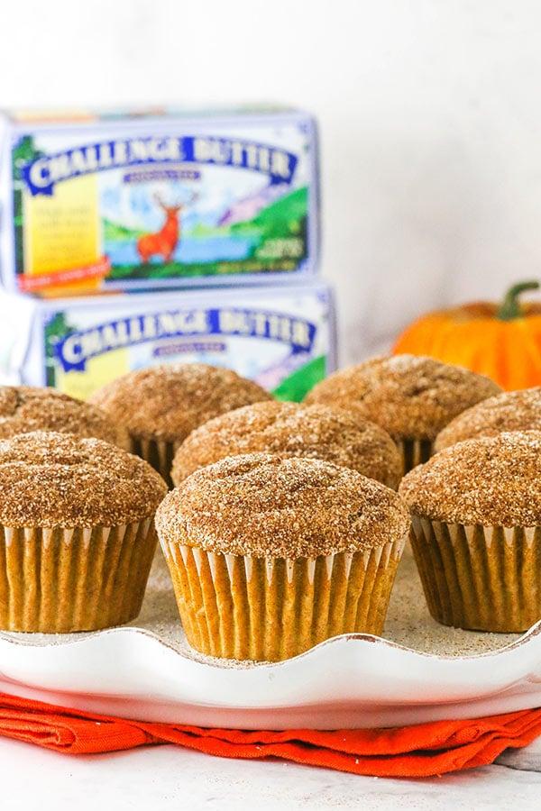muffin alla zucca e zucchero alla cannella sulla piastra bianca con burro sfida in background