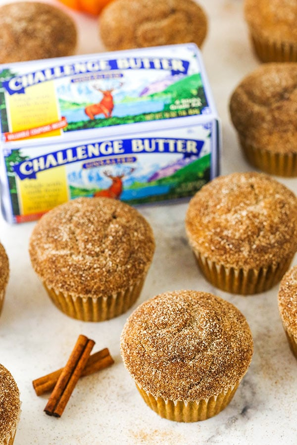 cinnamon sugar pumpkin muffins next to cinnamon sticks and challenge butter