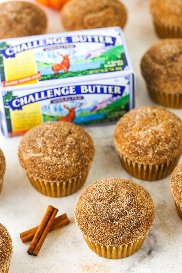 muffin alla zucca e zucchero alla cannella accanto a bastoncini di cannella e burro di sfida