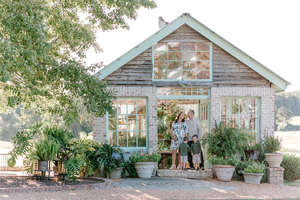family standing in doorway of greenhouse