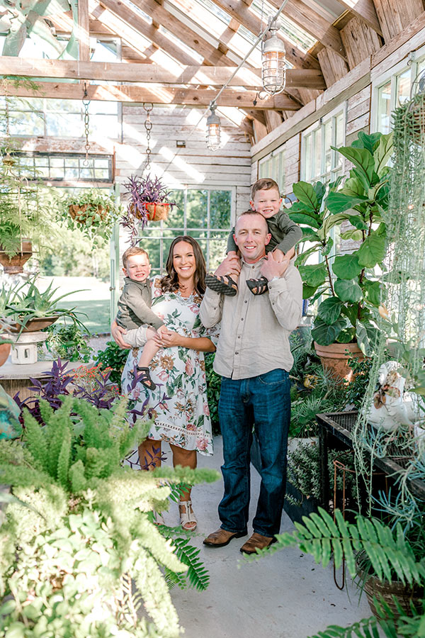 Family photo standing in greenhouse