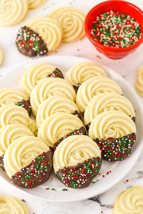 Butter Cookies Lined Up on a Plate Beside a Bowl of Sprinkles