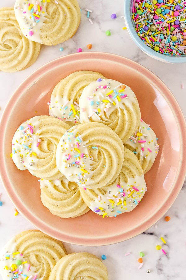White Chocolate Butter Cookies on a Pale Pink Plate Beside a Bowl of Pastel Sprinkles