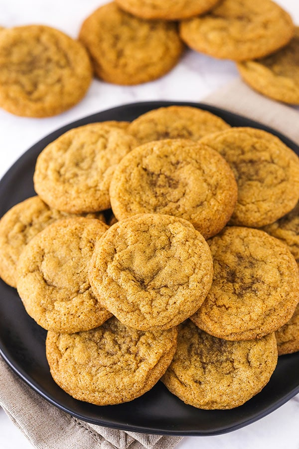 A Plate Full of Molasses Cookies With Five Stray Cookies on the Counter