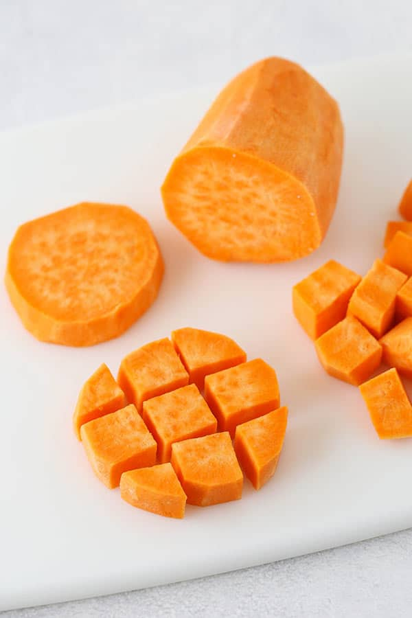 Half Inch Cubes of a Peeled Sweet Potato on a Cutting Board