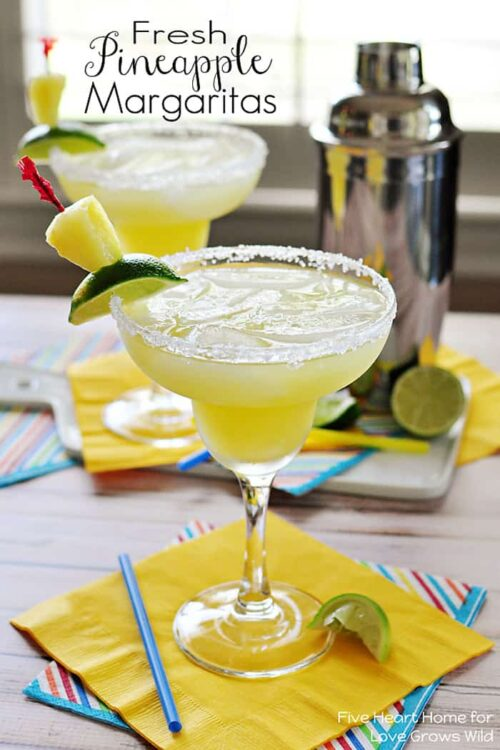 Two Frozen Pineapple Margaritas Garnished With Lime Slices and Chunks of Pineapple