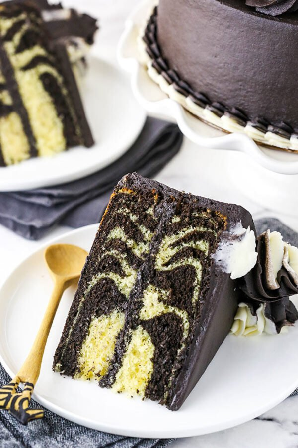 A Large Slice of Double-Layer Zebra Cake on a White Plate