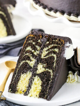 A Piece of Zebra Cake on a Plate with a Wooden Spoon
