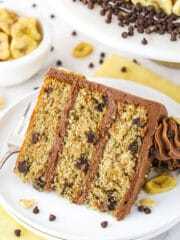 slice of banana chocolate chip cake on white plate with yellow napkin