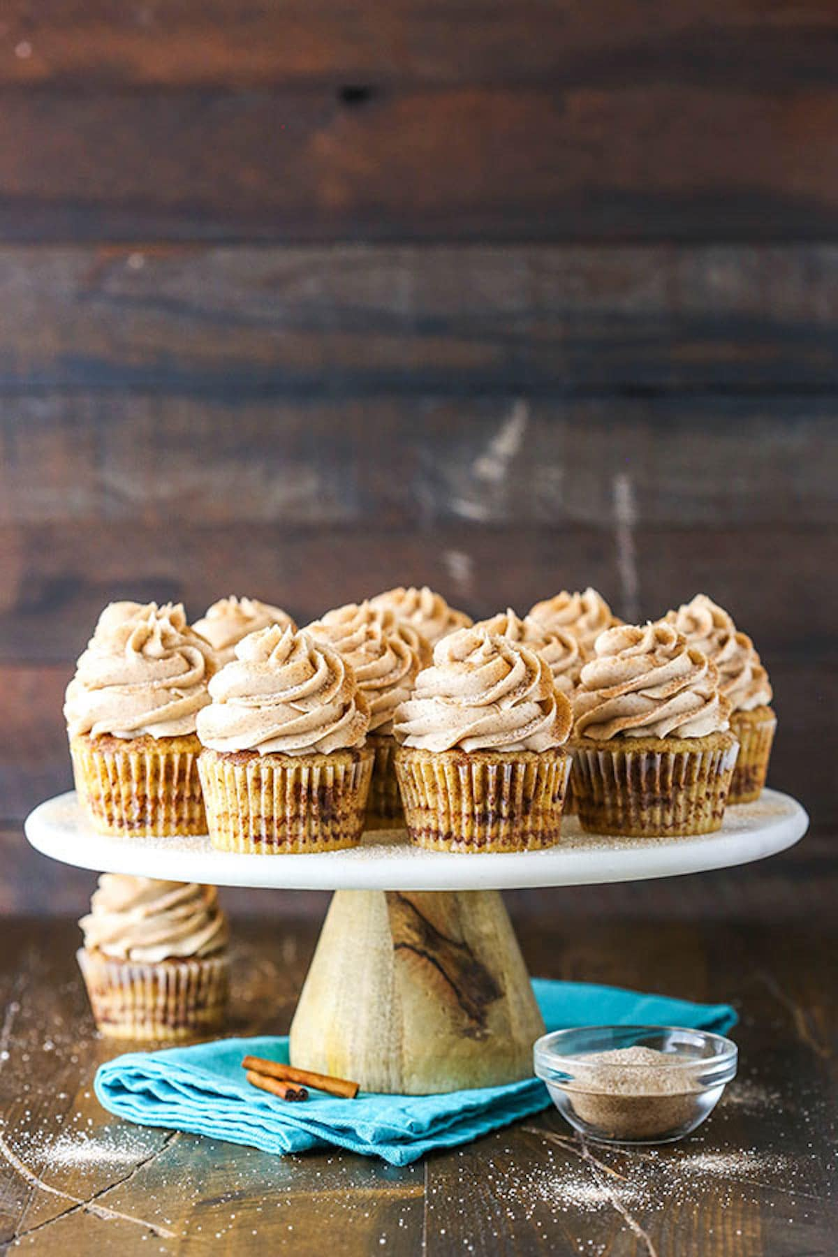 A Cake Stand Holding a Batch of Cinnamon Cupcakes in Front of a Wooden Wall