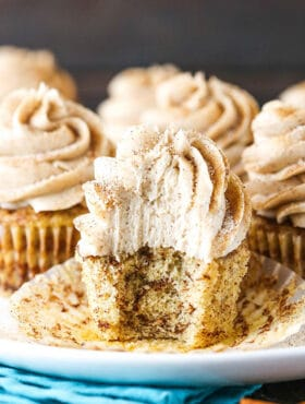 A Cinnamon Roll Cupcake on a Plate with One Bite Taken Out