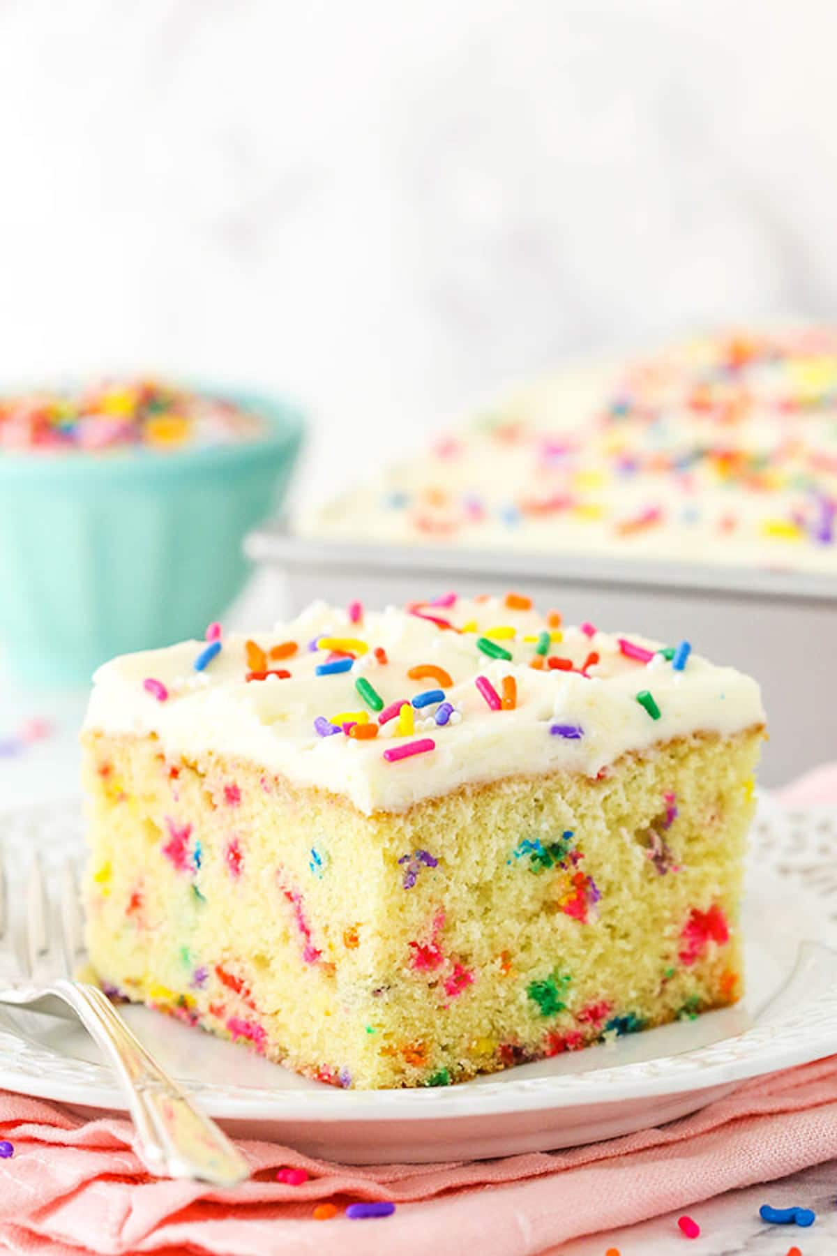A Piece of Funfetti Cake on a Plate with the Rest of the Cake in the Background