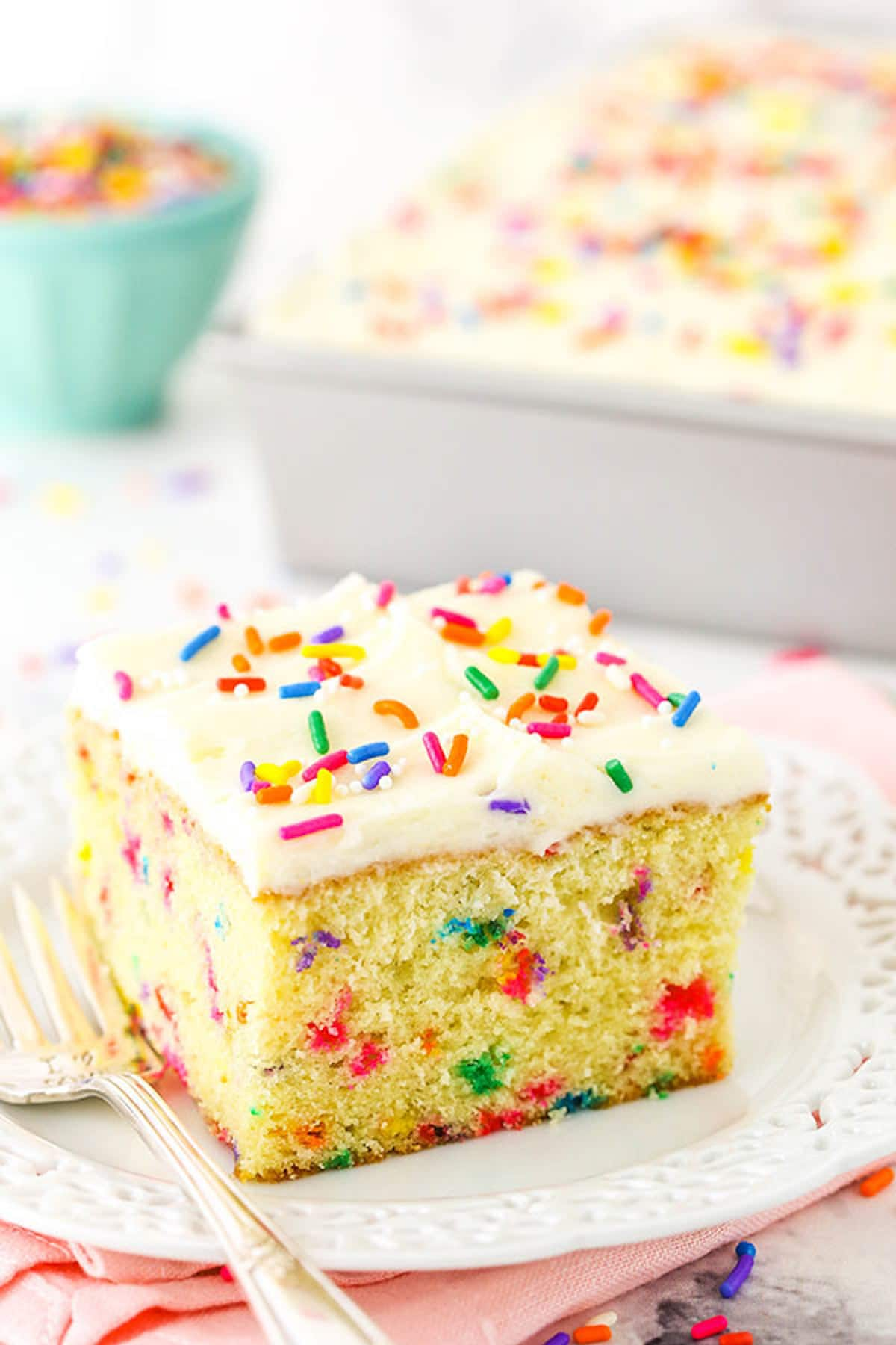 A Slice of Confetti Cake on a Plate with a Lace-Patterned Border