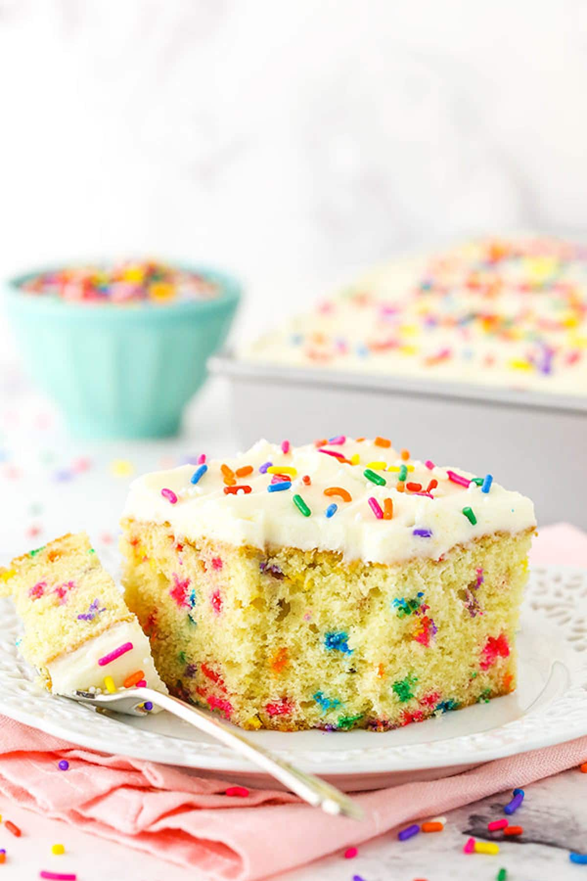 A Square Slice of Funfetti Cake with One Bite on a Metal Fork