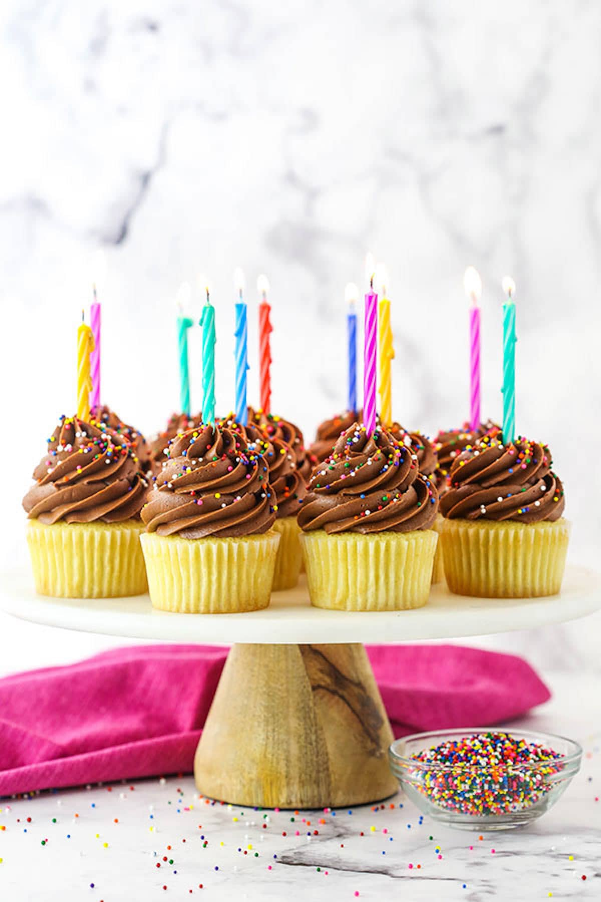 Chocolate Frosted Yellow Cupcakes with Colorful Candles On Them on a white tray