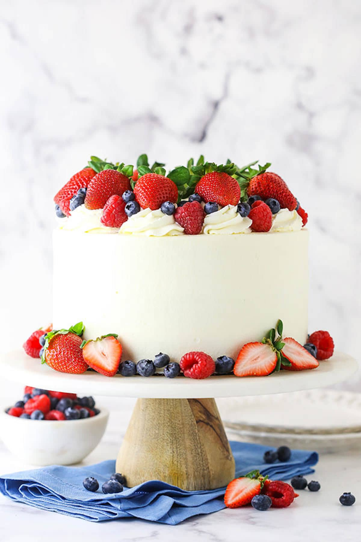 A Berry Chantilly Layer Cake on a Wooden Cake Stand Next to a Bowl of Berries and a Stack of Paper Plates