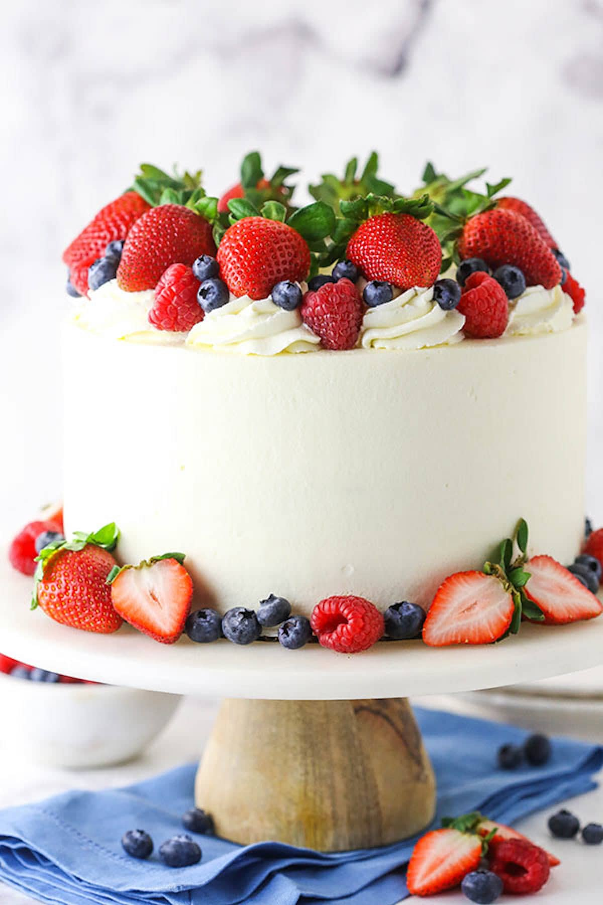 A Decorated Berry Layer Cake with Chantilly Cream Frosting on a Cake Stand