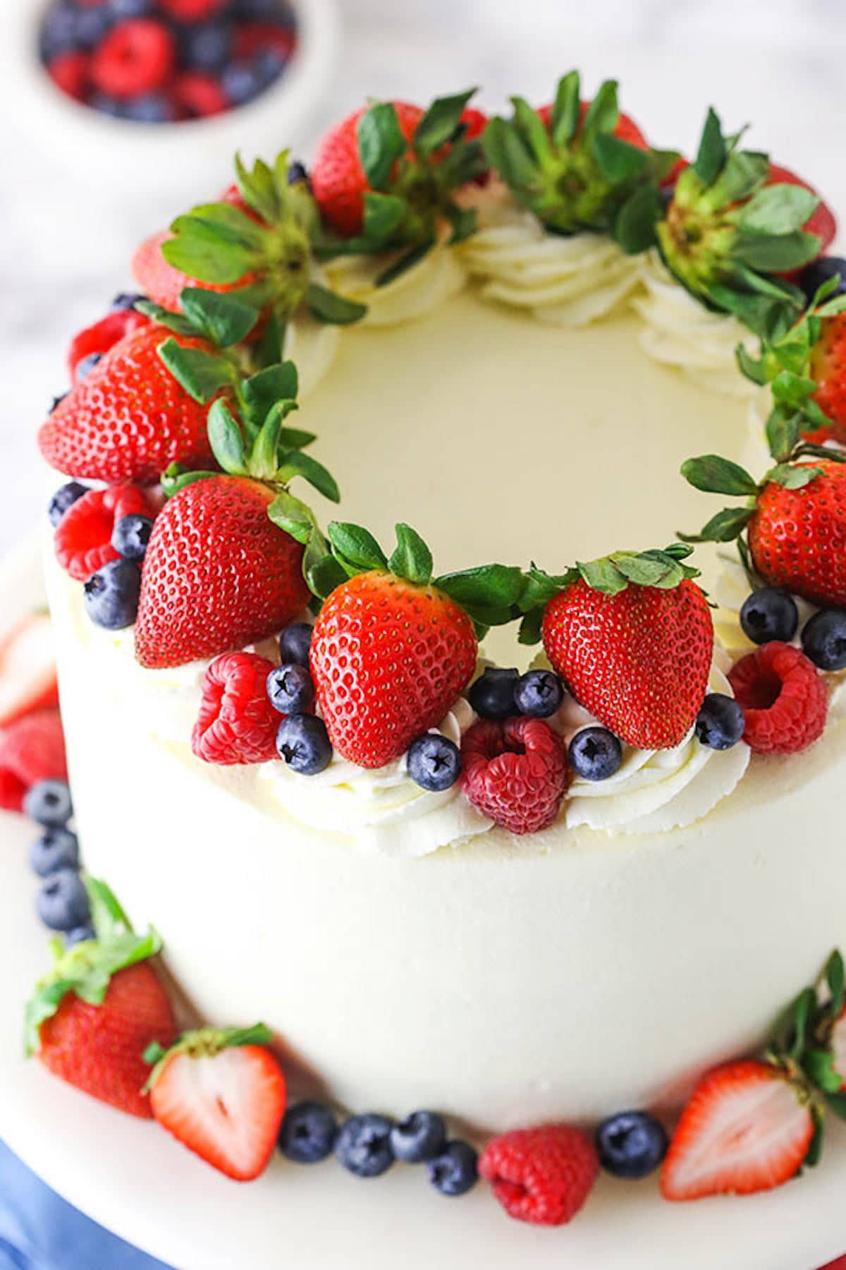 A Frosted Berry Chantilly Cake with a Ring of Strawberries, Blueberries and Raspberries on Top