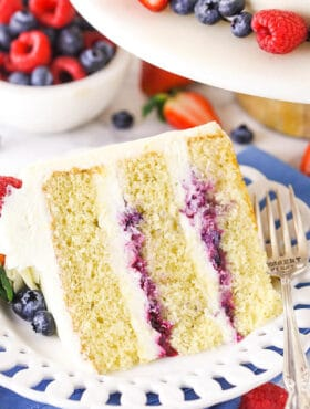 A Piece of Chantilly Layer Cake on a Plate with Fresh Berries