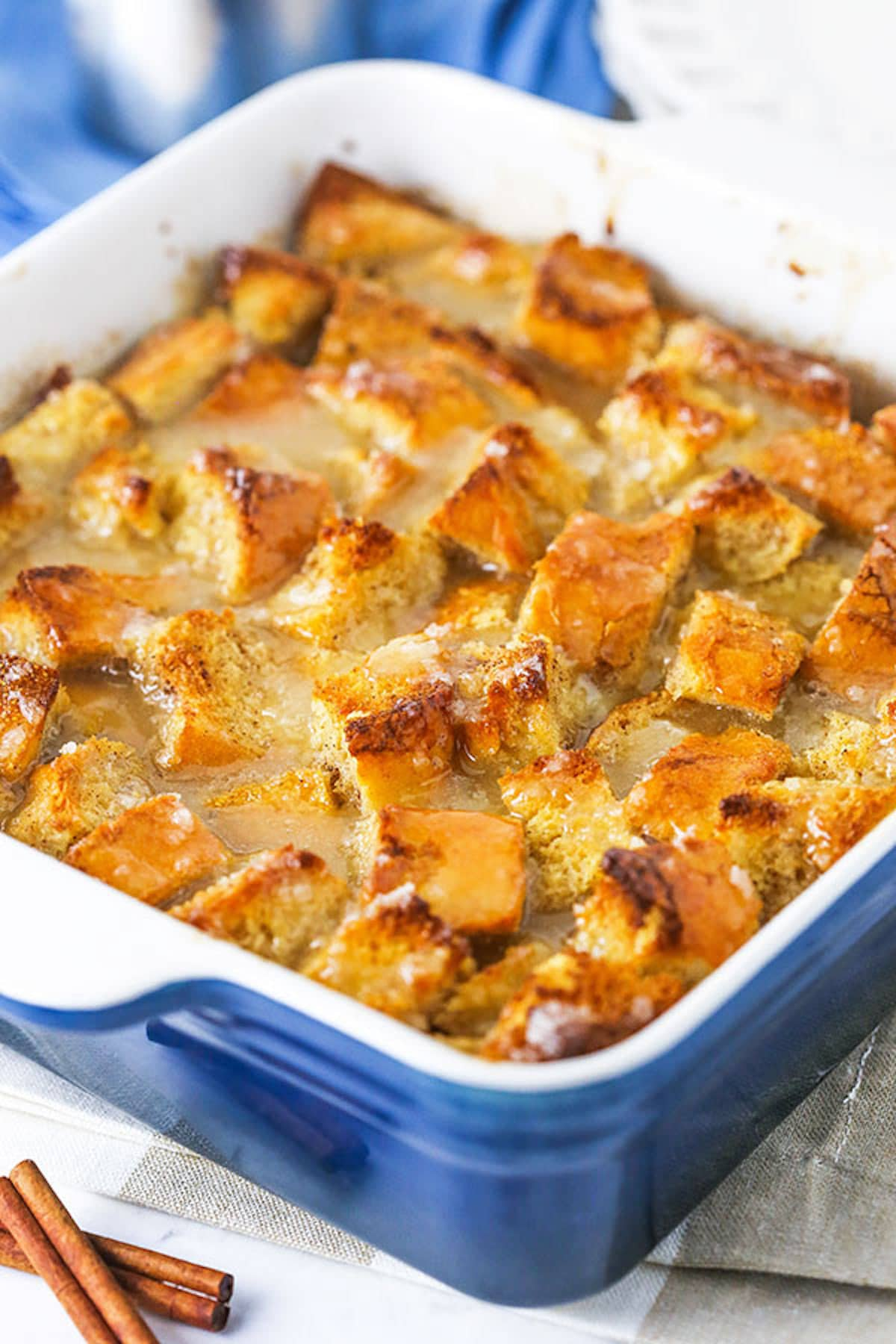 Freshly Baked Bread Pudding in a Pan Next to Two Cinnamon Sticks