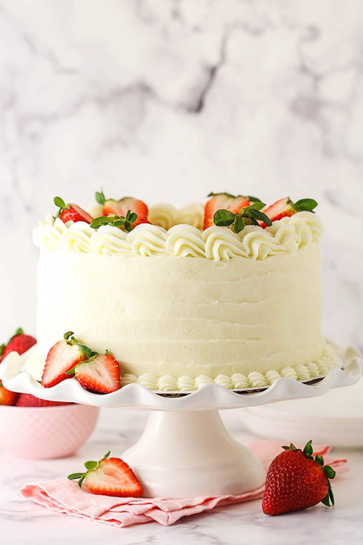 A Cake Stand Holding a Frosted Strawberry Layer Cake