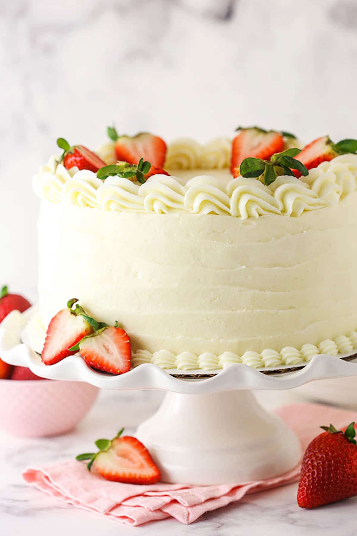 A Strawberry Cake with Cream Cheese Frosting on a White Cake Stand