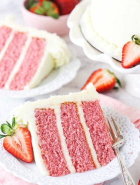 A Piece of Strawberry Cake on a Plate with a Sliced Strawberry Beside It